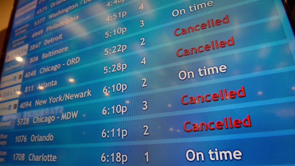 A screen shows canceled incoming flights at TF Green International Airport in Warwick, R.I. on March 30, 2020, during the novel coronavirus outbreak.