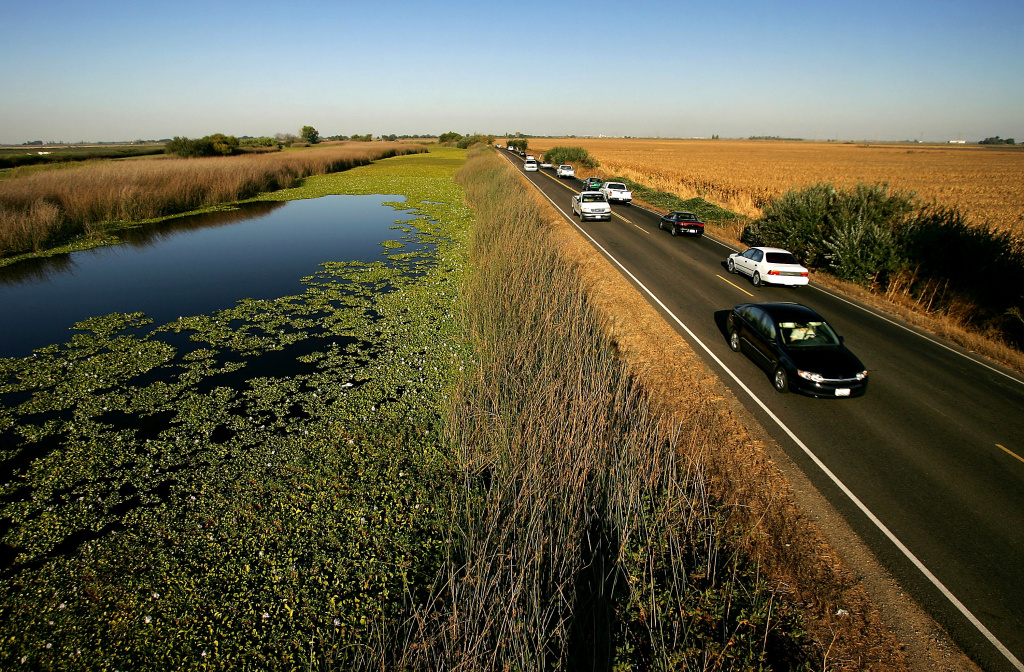 Water runs beside a lower-elevation farm (R) by a section of Highway 4 in the Sacramento-San Joaquin River Delta, west of Stockton, California.