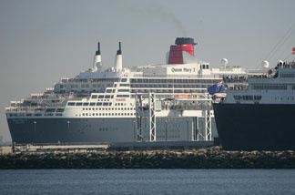 File photo: Long Beach - People stand on the bow of the Queen Mary (R) to view the Queen Mary 2 (L) as it enters Long Beach Harbor to meets her namesake ship, 23 February 2006.