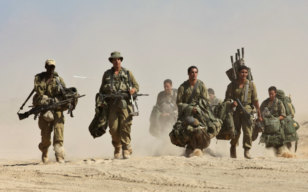 Israeli soldiers walk by foot near the border between Israel and the Gaza Strip as they return from the Hamas-controlled Palestinian coastal enclave on August 4, 2014.