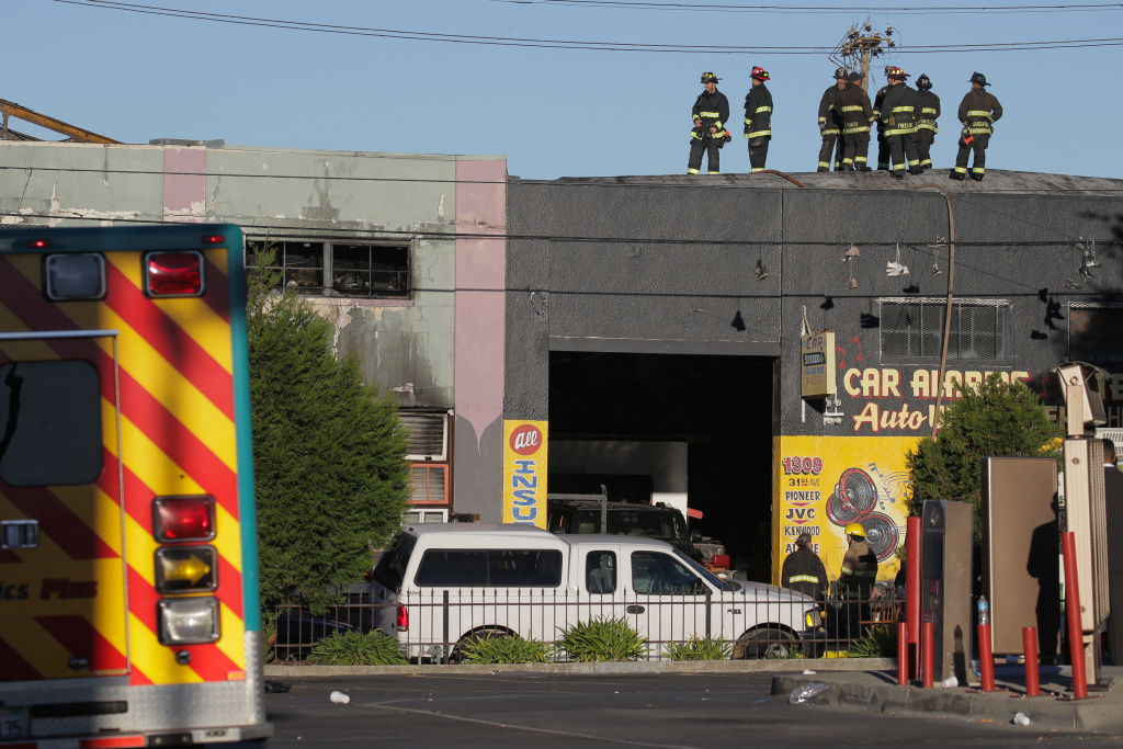 Firefighters investigate the Oakland fire that claimed the lives of at least 36 people.