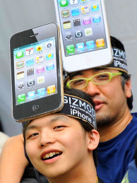 Two customers wait in line to purchase an iPhone 4 wearing iPhone placards on their heads.