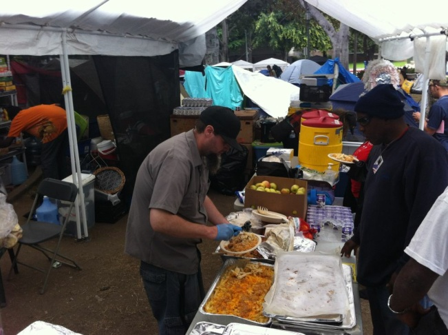 A member of Occupy Los Angeles serves Jennie Cook's catered meal for fellow demonstrators.