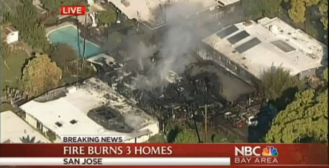 One home has been destroyed and others are threatened in a fire near a mall in San Jose Monday.