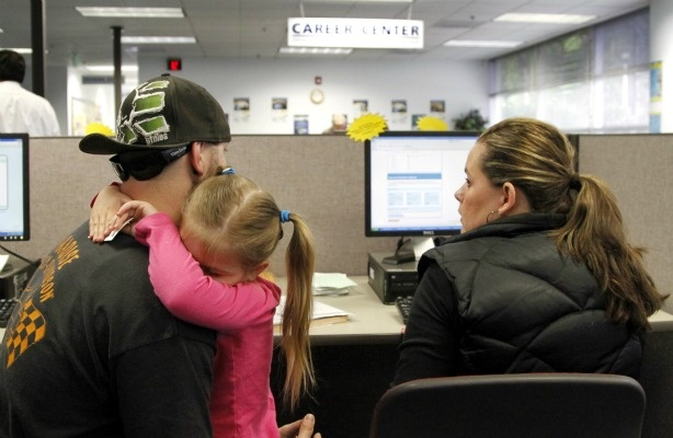 In this photo taken June 14, 2011, Matthew Weisker, left, holds his four-year-old daughter, Lexi Weisker, as he and his wife, Mindy, look for jobs in the database at Worksource Oregon in Tualatin, Ore.