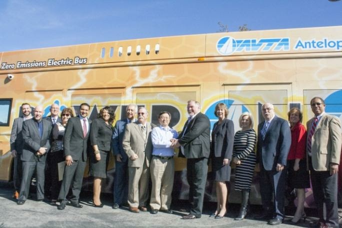 Transit officials and representatives from BYD Motors stand for a photo in 2016 after the transit agency voted to add more electric buses to its fleet