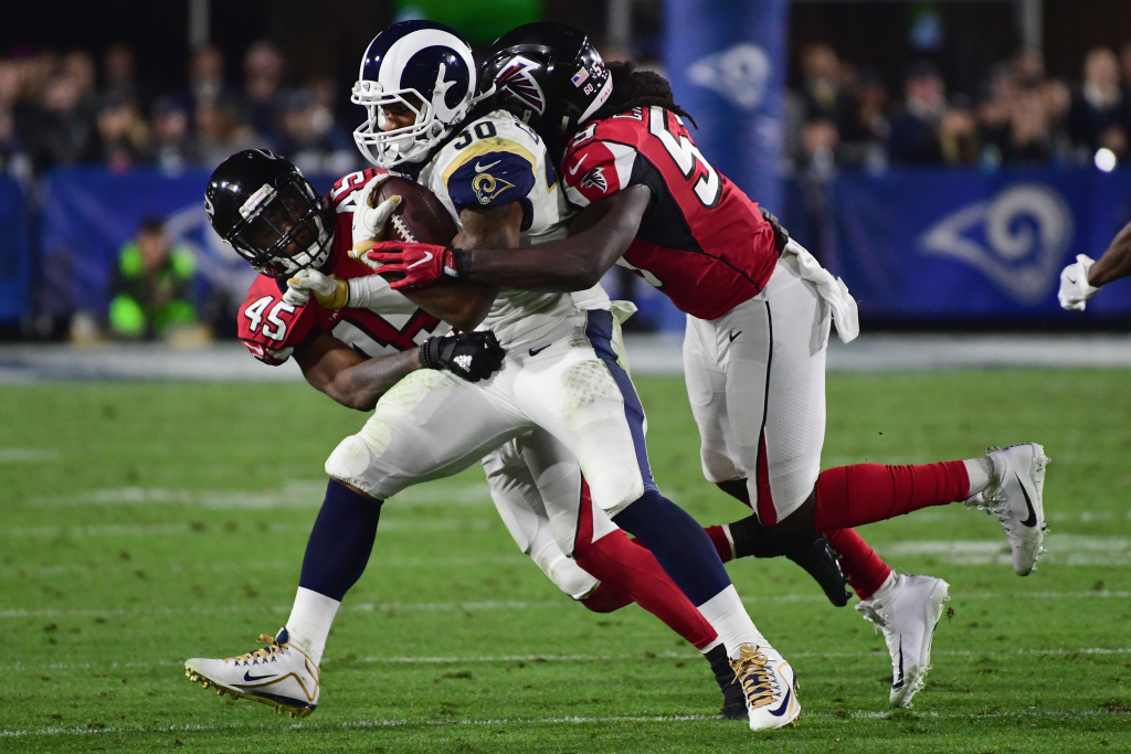 Running back Todd Gurley #30 of the Los Angeles Rams is tackled by middle linebacker Deion Jones #45 and outside linebacker De'Vondre Campbell #59 of the Atlanta Falcons during the NFC Wild Card Playoff game at Los Angeles Coliseum on January 6, 2018.