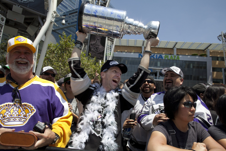 Anze Kopitar holds up the Stanley Cup while parading down Figueroa Street during a celebration for the Kings after beating the New York Rangers for the Stanley Cup.