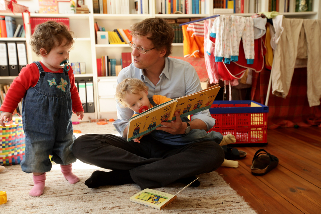 Oliver H., 42, a married federal employee on 6-month paternity leave, reads to his twin 14-month-old daughters Alma (R) and Lotte at his home on August 31, 2010 in Berlin, Germany.