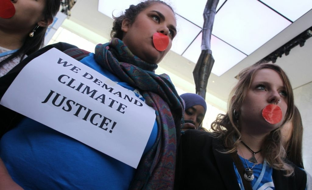 Local and international activists march inside a conference center to demand urgent action to address climate change at the UN climate talks in Doha, on December 7, 2012. UN climate negotiators locked horns on the final day of talks in Doha to halt the march of global warming, deeply divided on extending the greenhouse gas-curbing Kyoto Protocol and funding for poor countries.
