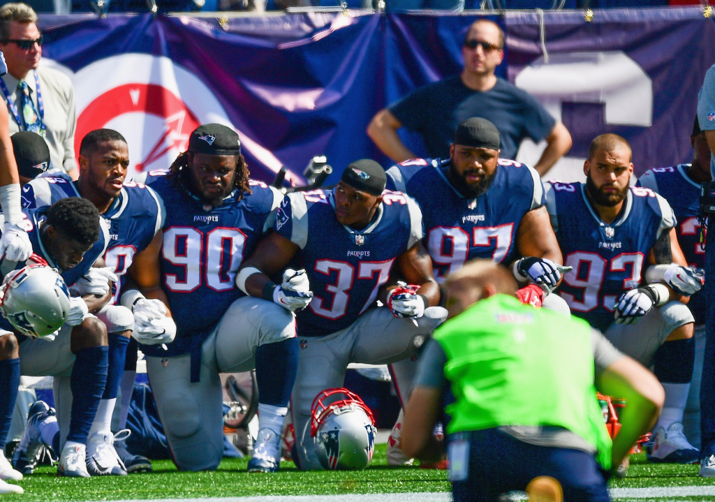 Members of the New England Patriots kneel on the sidelines during the national anthem at a game against the Houston Texans on September 24, 2017 in Foxboro, Massachusetts.