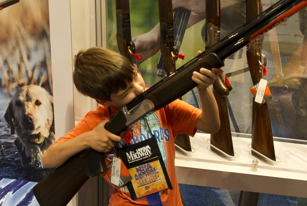 A boy under his parents' supervision, aims a shotgun.