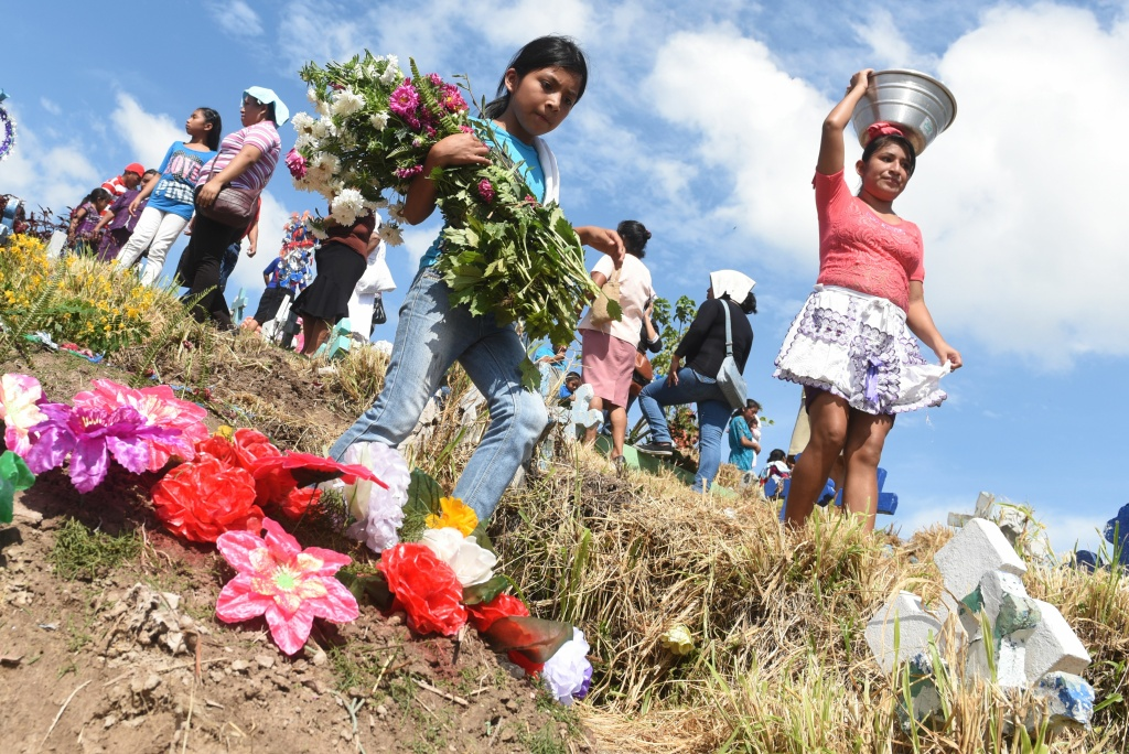 A girl takes flowers to the grave of a loved one during the commemoration of the day of the dead at a cemetery in Panchimalco, El Salvador on November 2, 2016.