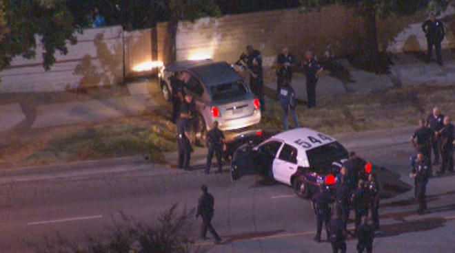 LAPD officers surround a car in Van Nuys. Officers fatally shot the male driver and took a female passenger into custody at the end of a chase.