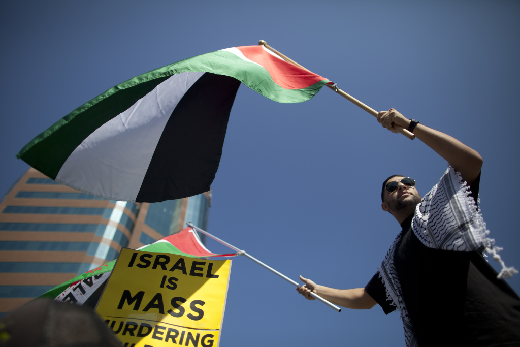Adbull Barakat of Simi Valley waves Palestinian flags during a recent protest in front of the Federal Building in Westwood. He spoke with his grandparents who live in Gaza and said they are stuck inside their home the Israeli military advances through the city.