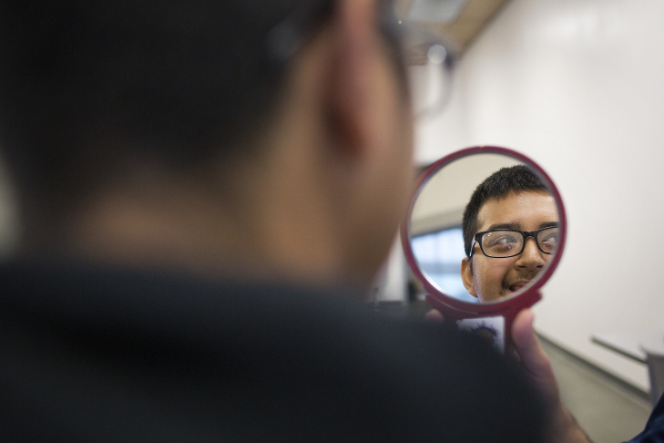 Jorge Valdez, program manager for Helen Keller International, holds up a mirror as freshman Celeste Garcia looks at her new prescription glasses on Friday, March 7 at Applied Technology Center High School in Montebello.