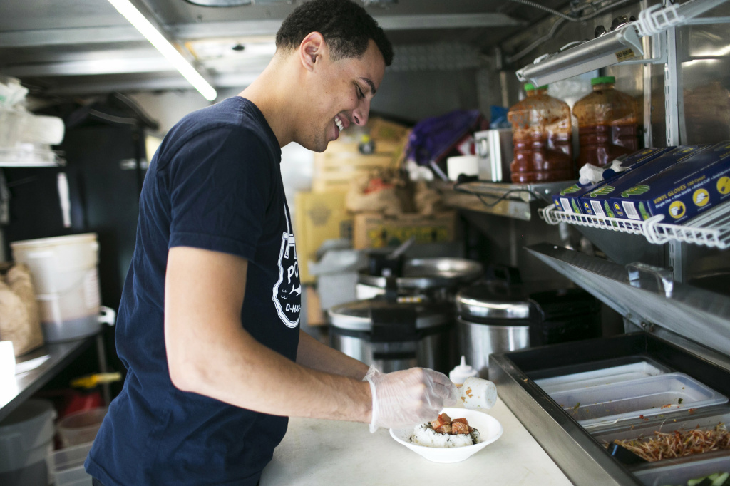Nile Woodson prepares a Hawaiian-style dish in his food truck, Hai Poké, in Columbus.