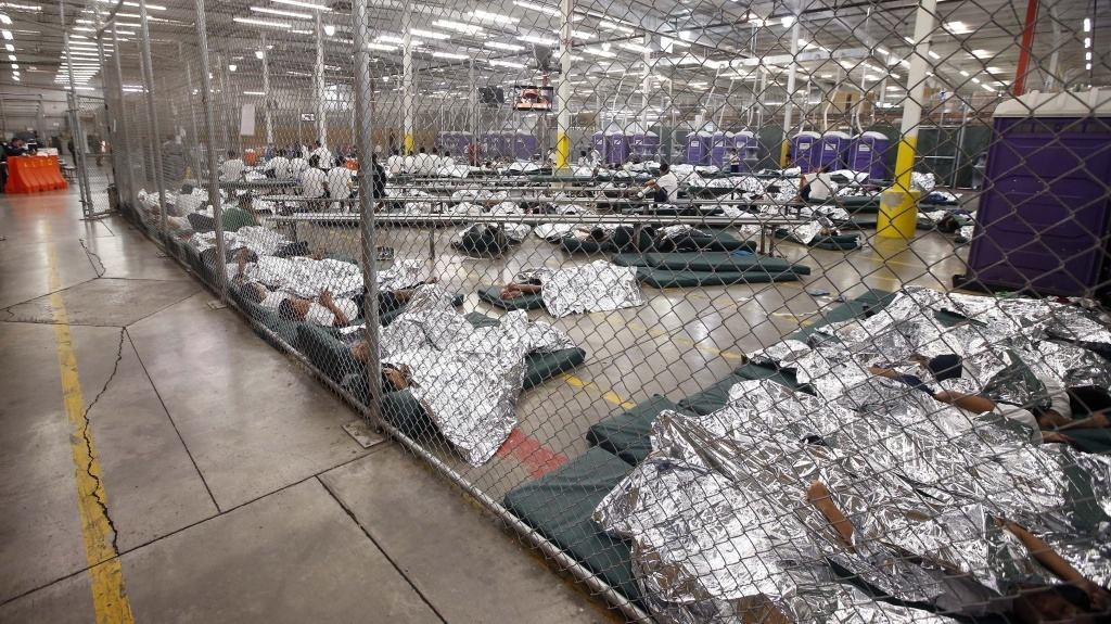 Detainees sleep and watch television in a holding cell where hundreds of mostly Central American immigrant children are being processed at a U.S. Customs facility in Nogales, Ariz.
