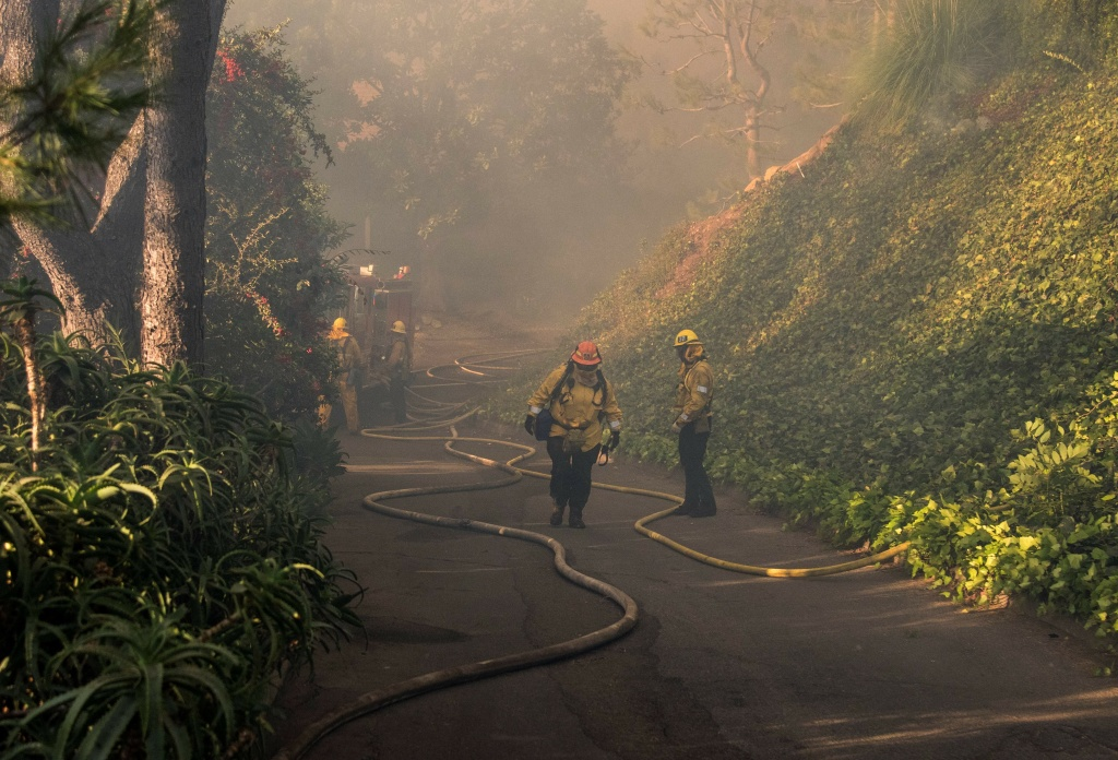 Firefighters work to save burning houses along Linda Flora Drive during the Skirball Fire in Los Angeles, California, December 6, 2017. The Skirball Fiire ignited before 5 a.m. on Wednesday and quickly engulfed 50 acres.