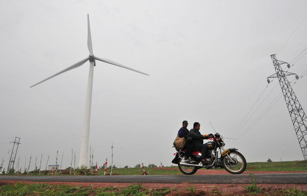 In a picture taken on June 16, 2009, commuters on a country road ride past a wind farm developed by state-owned China Energy Conservation Investment Corp in Zhangbei, north of Beijing in Hebei province. While a couple of years ago only a few dozen of the 80-metre (262-foot) propellor-like turbines stood on the wind farm's vast open expanse of grass, today there are 200 and counting.