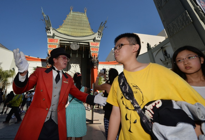 Chinese tourists walk past the TCL Chinese Theatre on Hollywood Boulevard in Hollywood, California on October 24, 2014. Local tourist officials say that mainland Chinese tourists numbers have quadrupled and now make up nearly half the number of foreign visitors to Los Angeles.