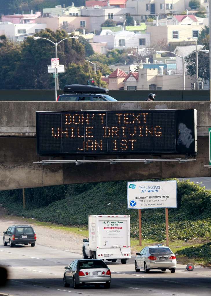 Cars drive by a sign notifying of 2009's new texting while driving law on Interstate 280 in San Francisco, California.