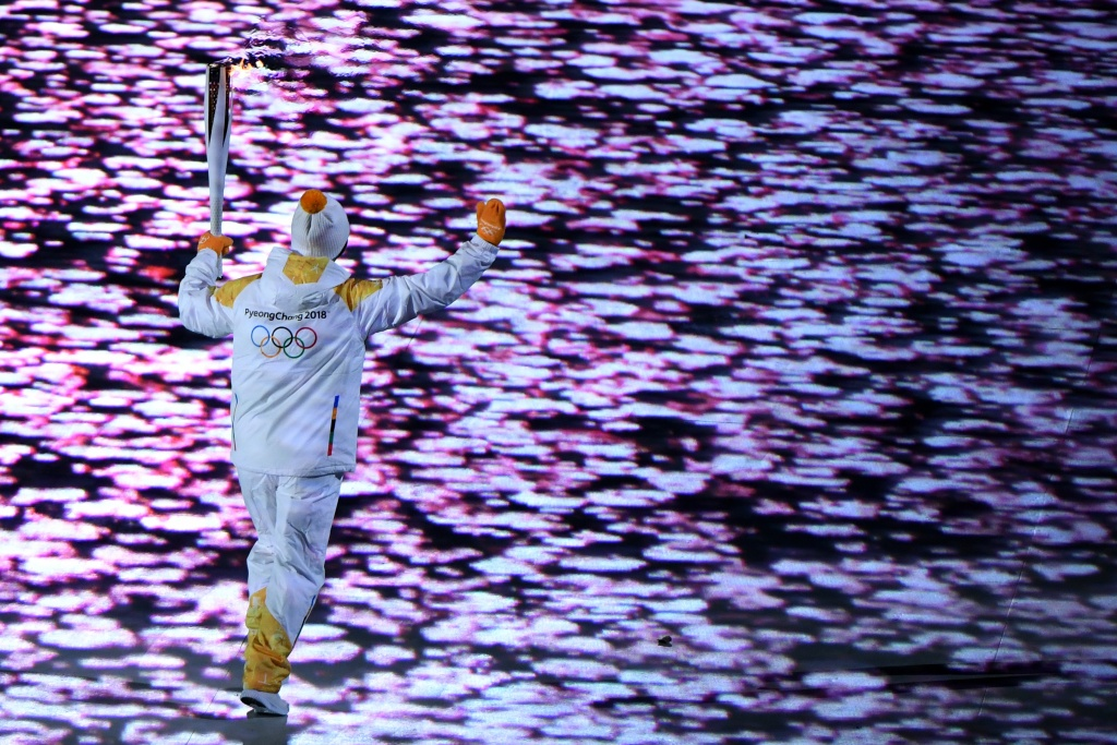 A torchbearer runs with the Olympic Flame during the Opening Ceremony of the Pyeongchang 2018 Winter Olympics on February 9, 2018.