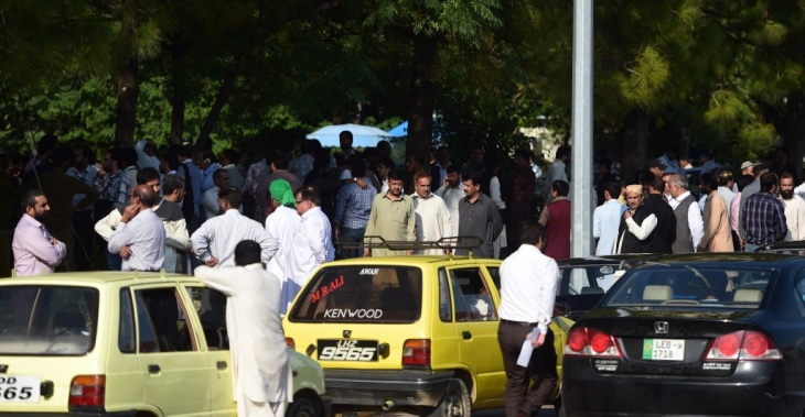 Pakistani federal employees gather outside their offices in Islamabad after Monday's deadly 7.5-magnitude earthquake.