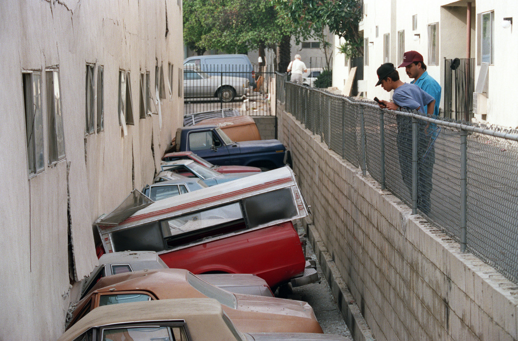 Two men inspect damage to cars and apartment complex after Northridge earthquake, on January 21, 1994, in Canoga, California. As the city prepares for the 20th anniversary of the quake, Mayor Eric Garcetti announced a new partnership with a U.S.G.S. seismologist to review the city's preparedness.
