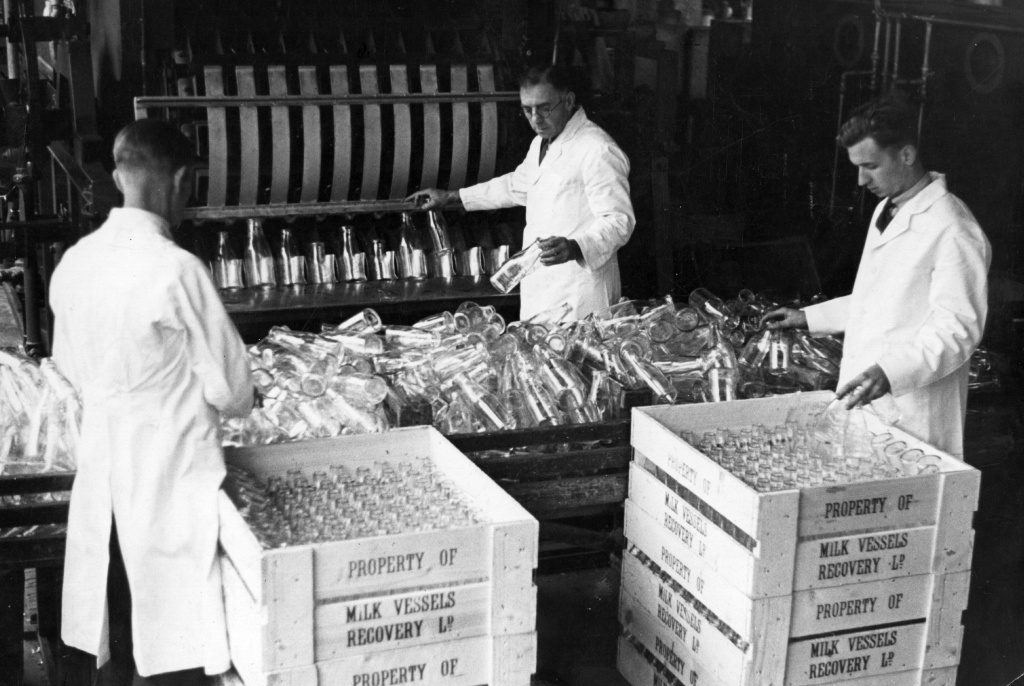 Circa 1930: Milk bottles are cleaned by machine and then collected and packed into crates by workers.