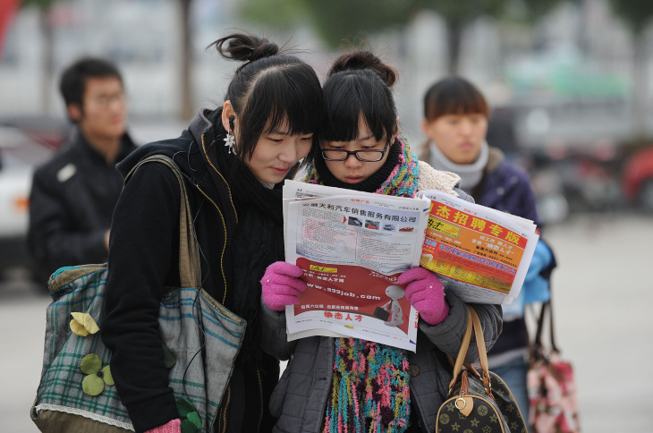 Chinese students look at a newspaper out