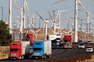 Emissions-producing diesel trucks and cars pass windmills along the 10 freeway near Banning, California.