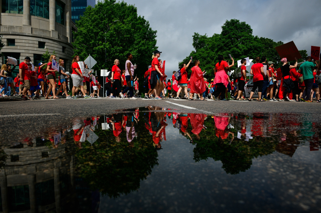 Teachers and supporters hold signs during a 'March For Students And Rally For Respect' protest in Raleigh, North Carolina on Wednesday, May 16, 2018.