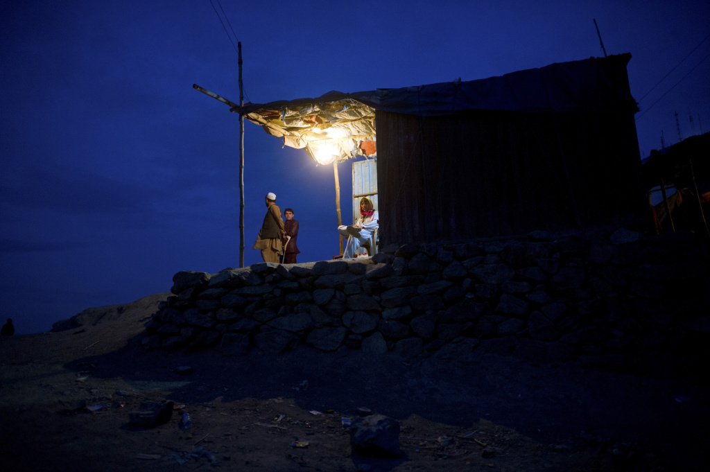 Afghans look on from a lit hut at dusk in Kabul on April 18, 2012.