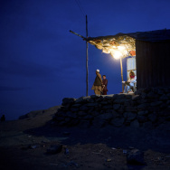 Afghans look on from a lit hut at dusk i