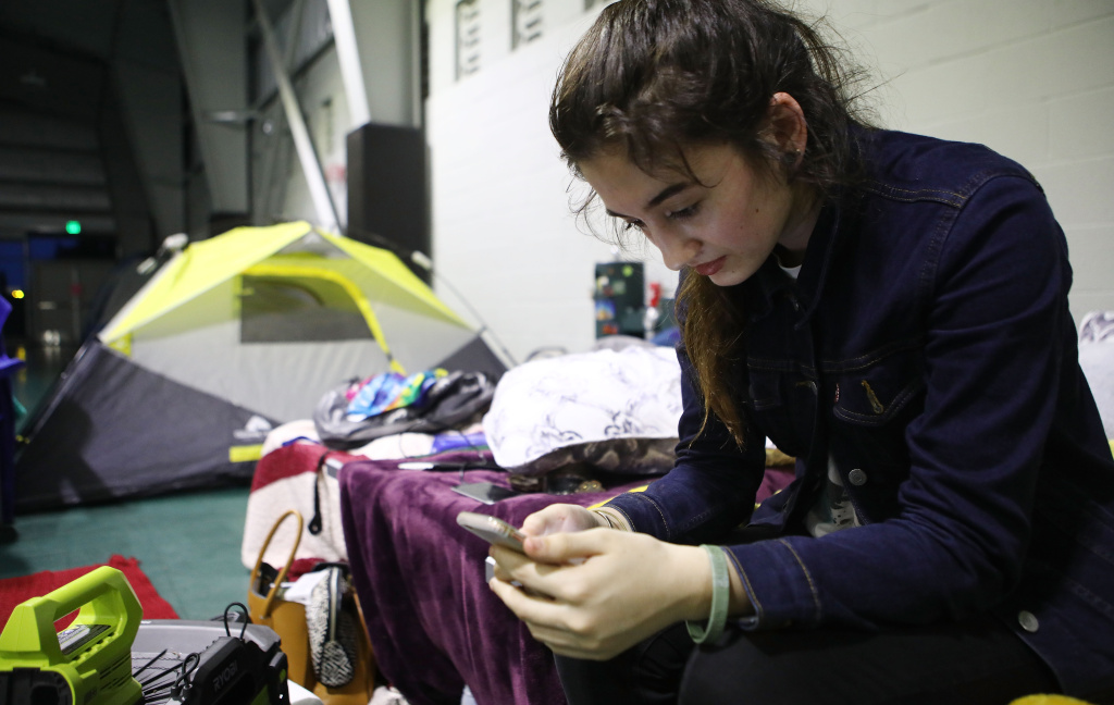 Evacuee Taylor Burns checks her phone in the emergency shelter where she is staying at the Pahoa Community Center on Hawaii's Big Island on May 5, 2018 in Pahoa, Hawaii. A magnitude 6.9 earthquake struck the island May 4 along with new eruptions from the Kilauea volcano.