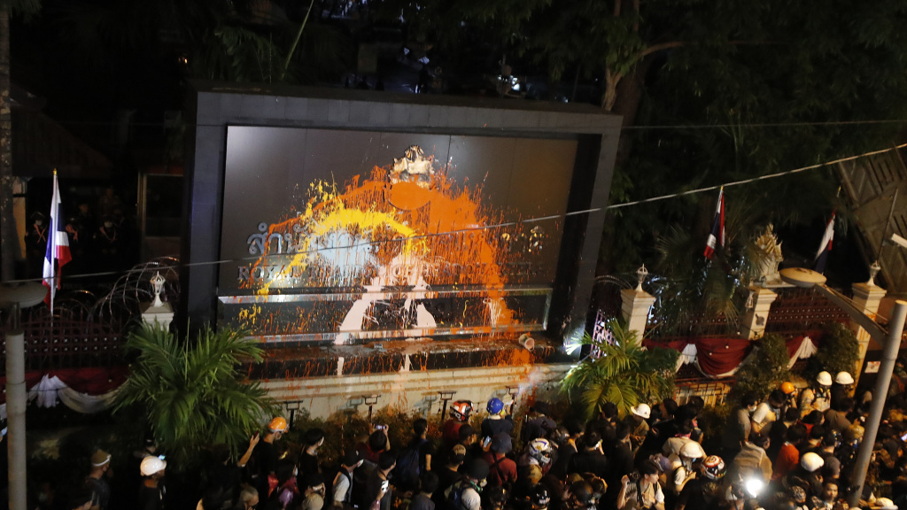 Pro-democracy protesters splash colored paint on the police headquarters sign in Bangkok, Thailand, on Wednesday.