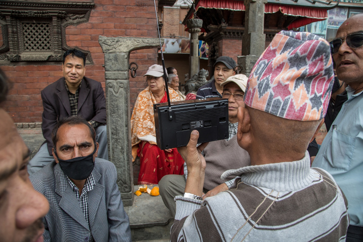 A group of people listen to news updates on a radio near Basantapur Durbar Square following an earthquake on April 25, 2015 in Kathmandu, Nepal. A major 7.8 earthquake hit Kathmandu mid-day on Saturday, and was followed by multiple aftershocks that triggered avalanches on Mt. Everest that buried mountain climbers in their base camps. Many houses, buildings and temples in the capital were destroyed during the earthquake, leaving hundreds dead or trapped under the debris as emergency rescue workers attempt to clear debris and find survivors.