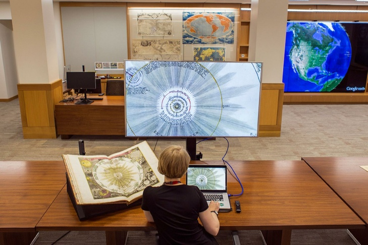 DeardraFuzzell, a cartographic technology specialist at Stanfordinspectsa 1742 celestial atlas in both paper and digital form at the new David Rumsey Map Center.