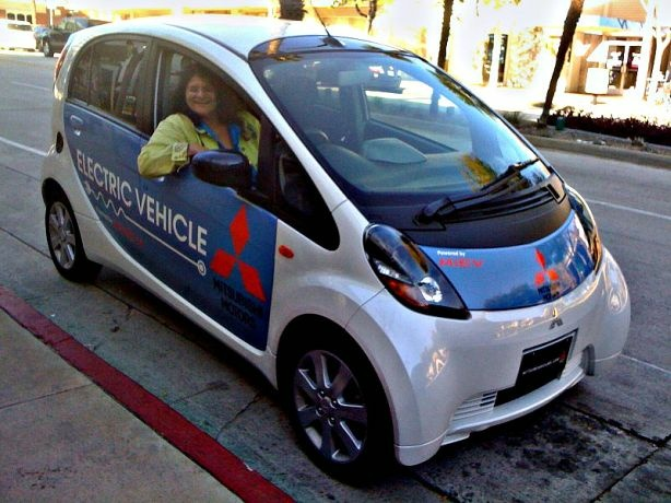 Shirley Jahad in a Mitsubishi electric iMiev prototype with the steering wheel on the right side.