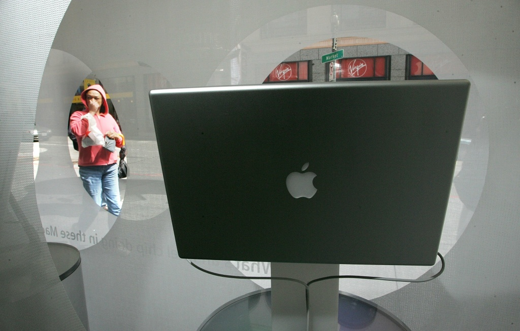 In this file photo, a woman looks at a window display featuring an Apple laptop at an Apple Store April 5, 2006 in San Francisco. For decades, the share of women majoring in computer science was rising. Then, in the 1980s, something changed.