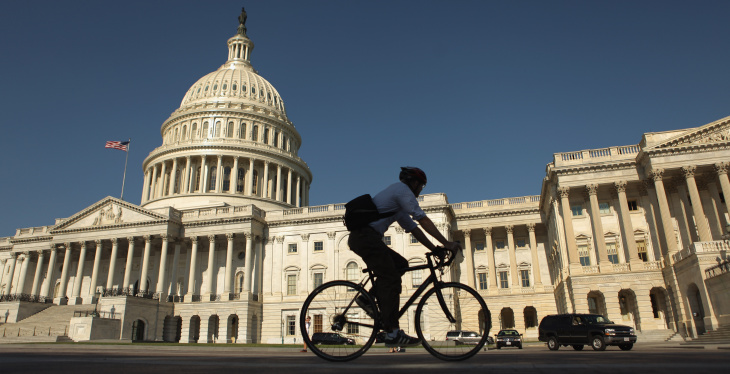 File: A bicyclist rides through the plaza on the east side of the U.S. Capitol August 2, 2011 in Washington, D.C.