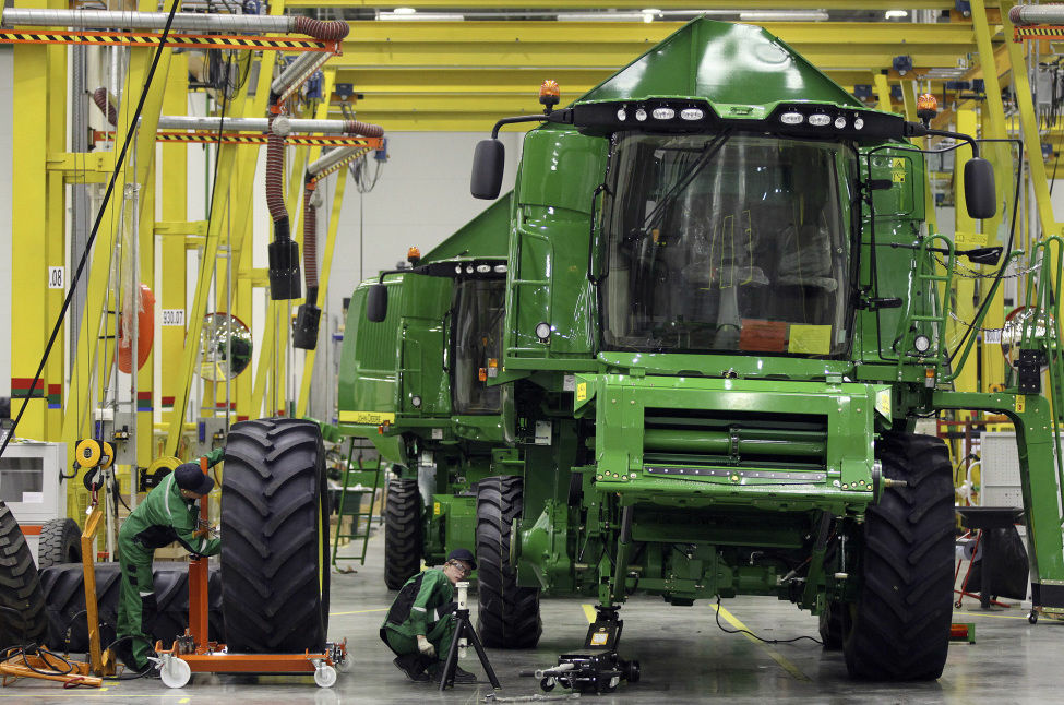 Employees fit a tire to a John Deere W540 combine inside the company's Domodedovo manufacturing center near Moscow, Russia. The U.S. trade deficit narrowed sharply in December because exports rose while oil imports plummeted. The trade deficit fell nearly 21 percent in December from November to $38.6 billion, the Commerce Department said Friday. That's the smallest in nearly three years. The smaller trade gap means the economy almost surely grew in the October-December 2012 quarter - an improvement from the government's estimate last week that it shrank in the final months of 2012.