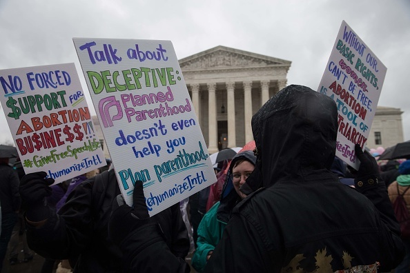 Anti-abortion activists demonstrate  in front of the US Supreme Court in Washington, DC, on March 20, 2018 as the court hears a challenge to California law requiring anti-abortion pregnancy clinics to distribute information on family planning services.