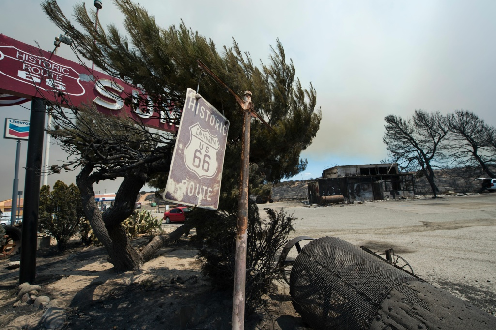 A Route 66 sign is one the only things still standing after the Blue Cut Fire burnt the historic Summit Inn diner to the ground overnight, at the top of the Cajon Pass in Hesperia, California, on August 17, 2016.