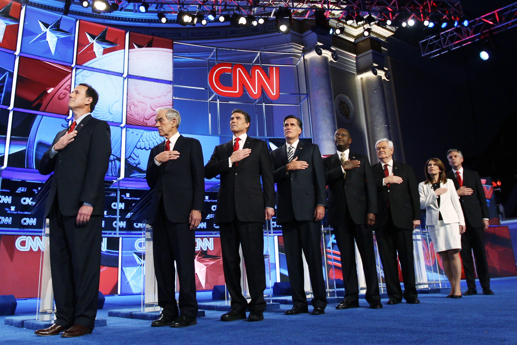 Republican presidential candidates (L-R) Rick Santorum, Rep. Ron Paul (R-TX), Texas Gov. Rick Perry, Mitt Romney, Herman Cain, Newt Gingrich, Rep. Michele Bachmann (R-MN), and Jon Huntsman listen to the national anthem prior to a debate at Constitution Hall Nov. 22, 2011, in Washington, D.C. The debate, hosted by CNN and in partnership with the Heritage Foundation and the American Enterprise Institute, focused primarily on national security, foreign policy and the economy.
