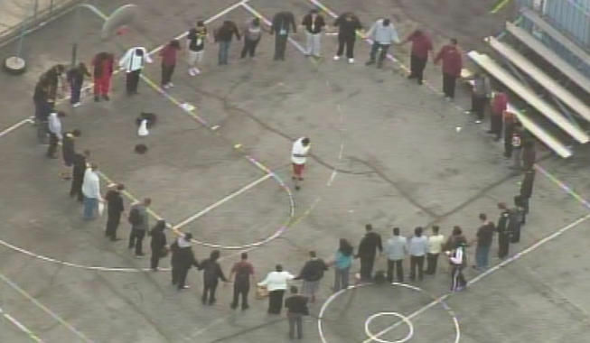 A group holds hands in a circle on the grounds of a Hollywood school where a counselor was fatally stabbed.