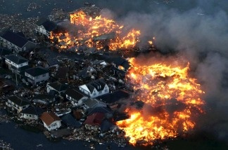 This aerial shot shows houses in flame after being hit by a tsunami at Natori city in Miyagi prefecture, northern Japan on March 11, 2011.