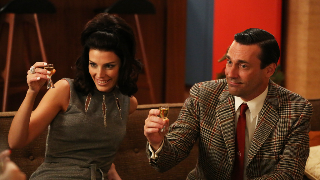 Megan Draper (Jessica Pare) and Don Draper (Jon Hamm) raise their glasses. Many fans have been inspired to do the same, but <em>Mad Men </em>has a complicated relationship with alcohol.