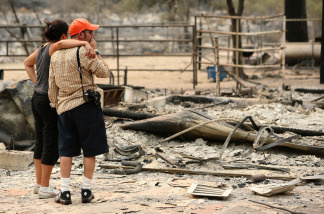 A resident is consoled by a friend as he sees the charred remains of his home that was burned by the Station Fire at Vogel Flats near Tujunga, California.